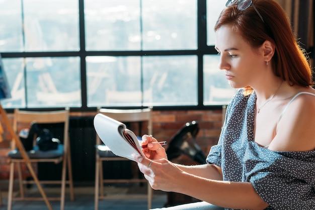 Dessin d'artiste. espace de travail studio. femme peintre faisant des croquis au crayon dans le bloc-notes.