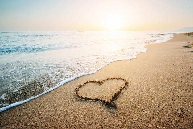 Dessin coeur sur sable jaune sur le coucher de soleil fantastique