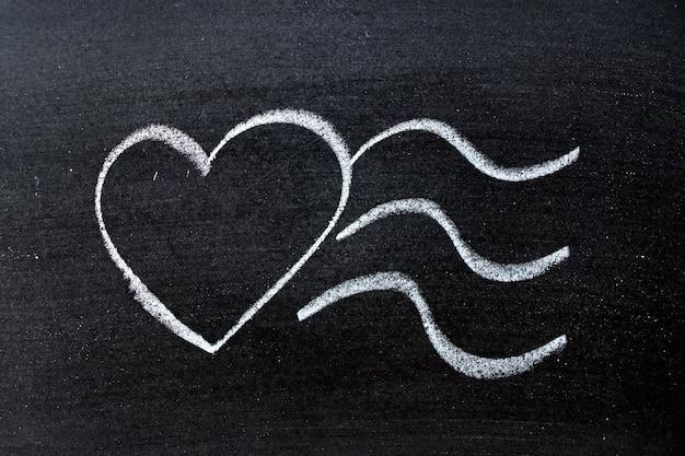 Dessin à la craie en forme de cœur avec des vagues sur la surface de l'ardoise
