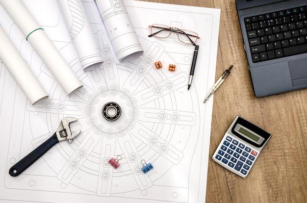 Dessin industriel avec différents outils de dessin, calculatrice et ordinateur portable