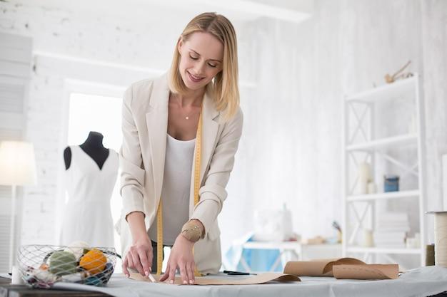 Dessin de modèle. heureux tailleur féminin utilisant cale tout en travaillant avec un motif