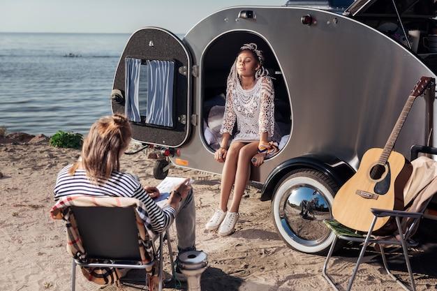 Dessin de petit ami. femme rayonnante attrayante avec des dreadlocks assis dans une remorque compacte pendant que son petit ami dessin