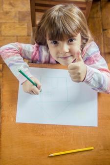Dessine la famille de la maison de l'enfant. mise au point sélective. des gamins.