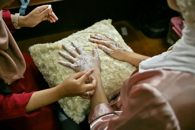 Dessiner mehndi ou le henné sur les mains de la mariée