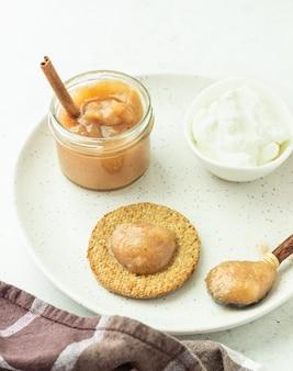 Dessinez des craquelins de grains entiers croustillants avec du yogourt naturel et de la confiture sur une assiette grise. petit déjeuner ou collation simple.