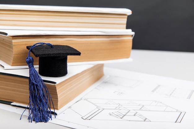 Dessins mécaniques et chapeau de graduation sur le concept d'enseignement de l'ingénierie des livres