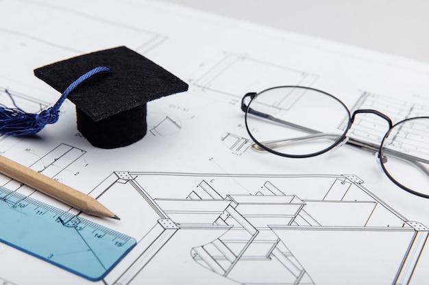 Dessins techniques et concept de formation en ingénierie en gros plan sur le chapeau de graduation