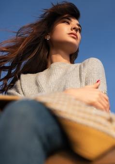 De dessous de charmante femme pensive en pull tricoté à la recherche de suite dans les pensées