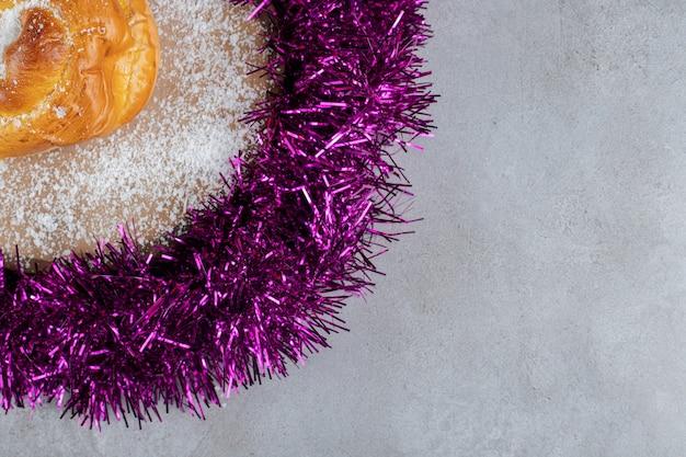 Dessous de guirlande violette avec un petit pain sur une surface en marbre