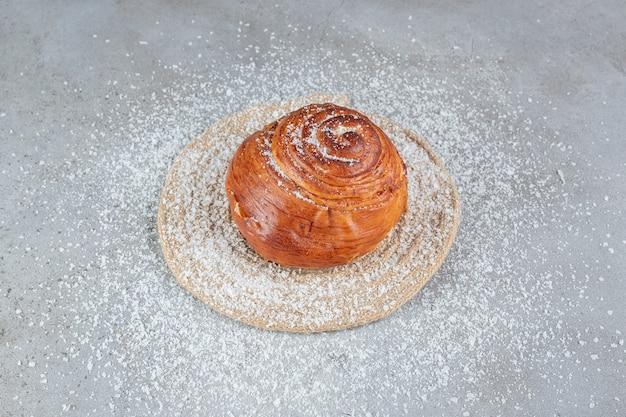 Dessous de plat sous un petit pain sucré sur une surface en marbre