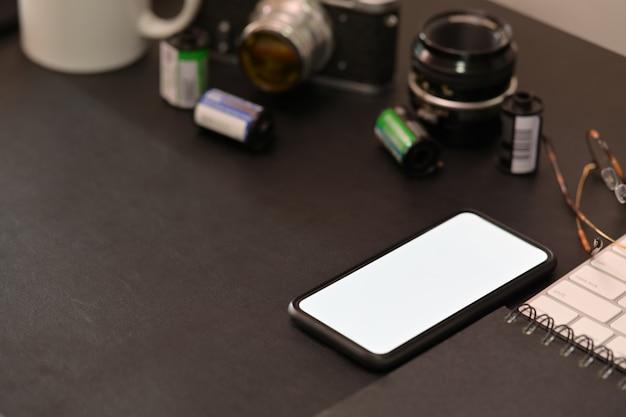Dessus de bureau lerther foncé du photographe avec téléphone portable à écran blanc, appareil photo vintage, films, lunettes, café et espace de copie