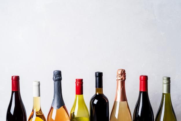 Dessus de différentes sortes nouvelles bouteilles de champagne, blanc, vin rouge sur fond clair