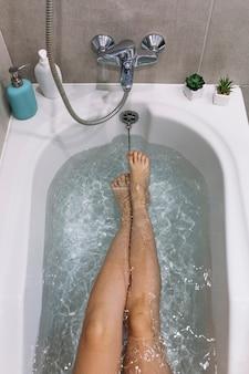 De dessus les jambes dans la baignoire