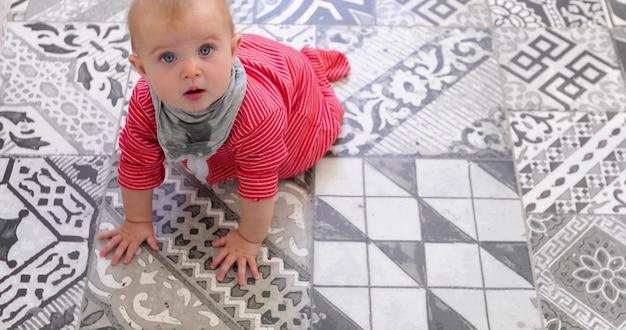 De là-dessus, joli bébé en bavette grise rampant sur un sol carrelé noir et blanc et regardant la caméra à l'intérieur