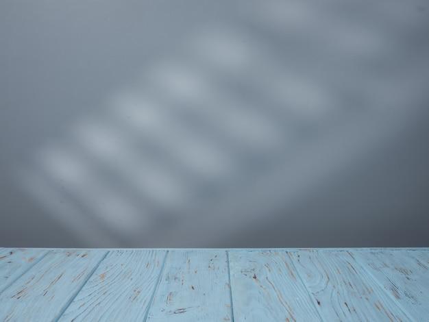 Dessus de table bleu pour la présentation du produit et éclairage de la fenêtre au mur