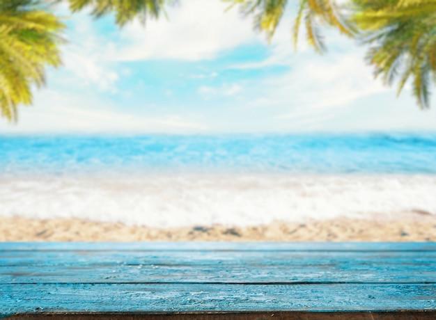 Dessus de table bleu vide contre un espace de plage avec la mer et les palmiers (maquette)