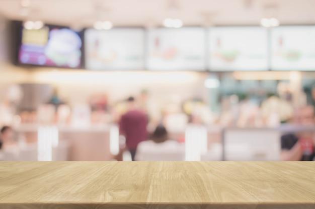 Dessus de table en bois et arrière-plan flou intérieur de restaurant avec filtre vintage - peut utilisé pour l'affichage ou le montage de vos produits.