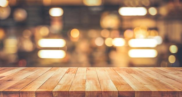 Dessus de table en bois avec bokeh or clair flou au café