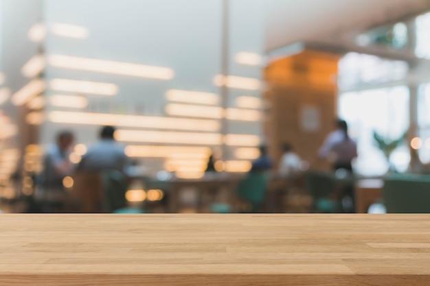 Dessus de table en bois et café bokeh floue et fond intérieur de café-restaurant avec filtre vintage - peut utilisé pour l'affichage ou le montage de vos produits.