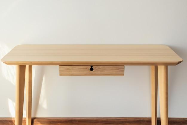 Dessus de table en bois clair vide avec fond de mur blanc