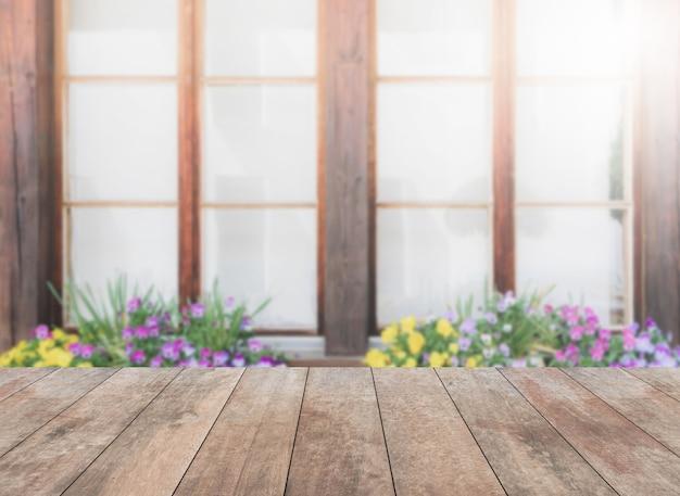 Dessus de table en bois et fleurs floues et fond de fenêtre avec filtre vintage