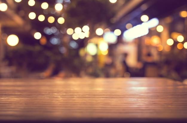 Dessus de table en bois avec flou d'éclairage dans un café-restaurant de nuit