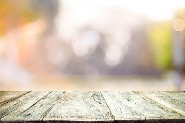 Dessus de table en bois sur fond abstrait de bokeh.
