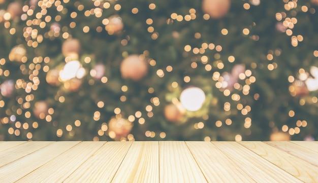 Dessus de table en bois avec lumière de bokeh festive de vacances de noël abstraites sur fond flou d'arbre pour l'affichage du produit de montage