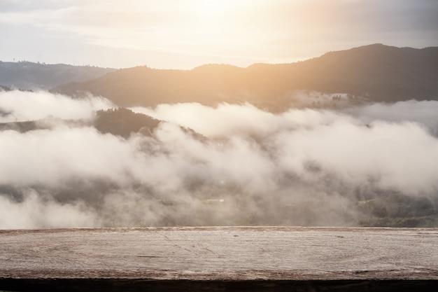 Dessus de table en bois avec la montagne avec fond de paysage de brouillard.