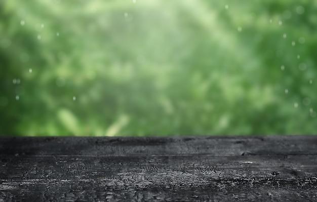 Dessus de table en bois noir sur fond vert flou pour la publicité