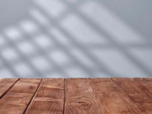 Dessus de table en bois pour la présentation du produit avec éclairage de fenêtre au mur