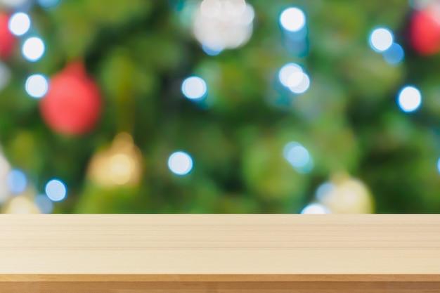 Dessus de table en bois vide avec arbre de noël flou abstrait avec fond clair de décoration bokeh pour l'affichage du produit