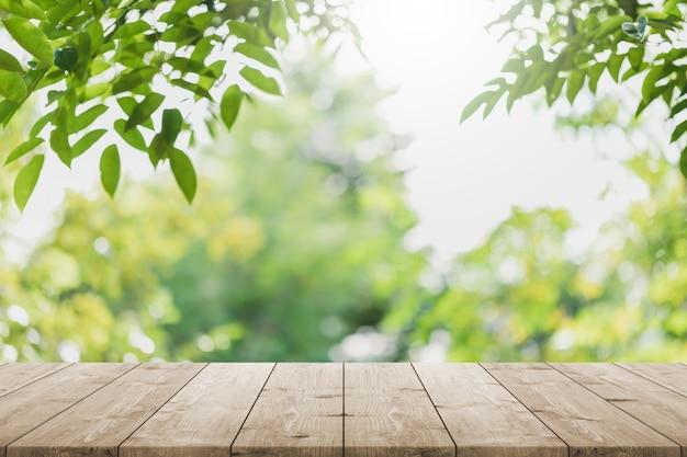 Dessus de table en bois vide et arbre vert flou dans le jardin du parc