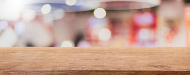 Dessus de table en bois vide et arrière-plan intérieur flou du café et du restaurant - peuvent être utilisés pour l'affichage ou le montage de vos produits.