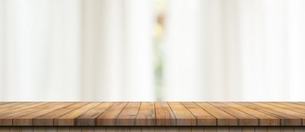 Dessus de table en bois vide sur la fenêtre blanche flou