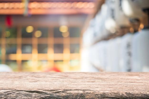 Dessus de table en bois vide et fenêtre en verre flou intérieur restaurant et café