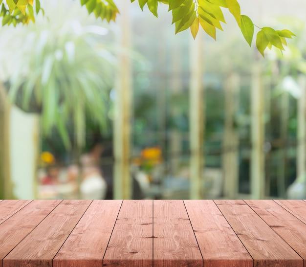 Dessus de table en bois vide et floue de la pièce intérieure avec vue de la fenêtre du fond du jardin.