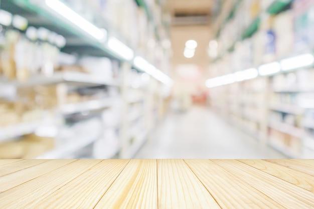 Dessus de table en bois vide avec fond d'allée de supermarché ou d'entrepôt flou