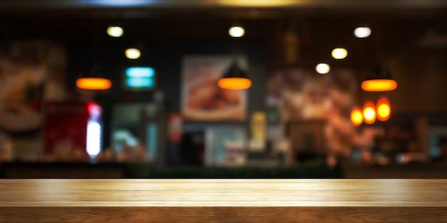 Dessus de table en bois vide avec fond de café ou de restaurant flou, panoramique