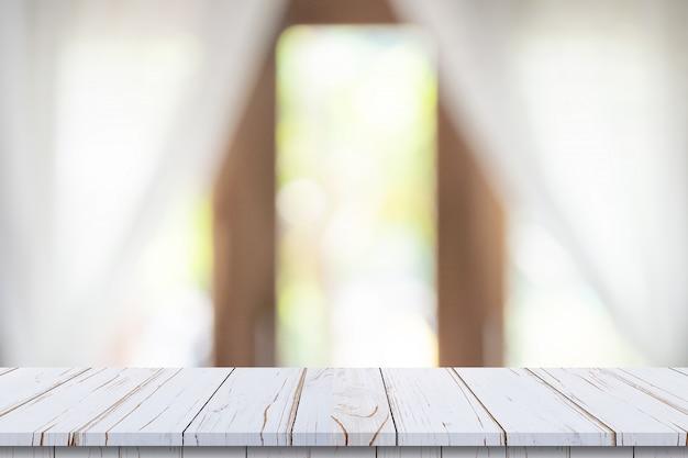 Dessus de table en bois vide sur fond de fenêtre blanche flou. pour le montage de produits ou d'aliments.