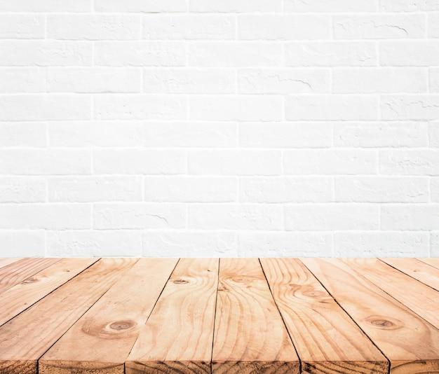 Dessus de table en bois vide avec fond de mur de brique blanche.