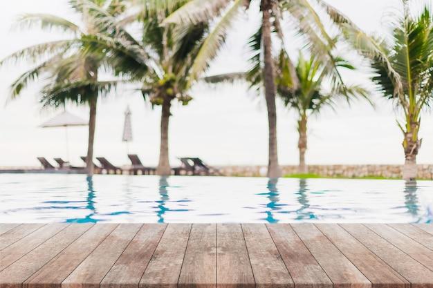 Dessus de table en bois vide et piscine floue dans une station balnéaire tropicale en été