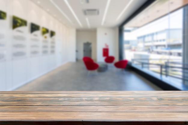 Dessus de table dans une grande pièce floue en arrière-plan avec une grande fenêtre et des canapés rouges.