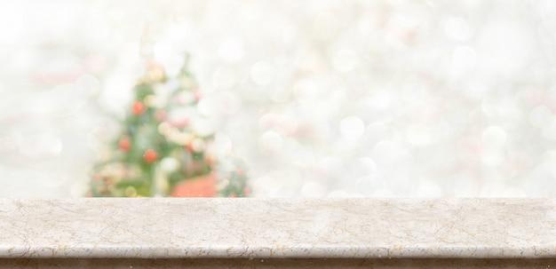 Dessus de table en marbre blanc au décor flou d'arbre de noël bokeh avec fond clair