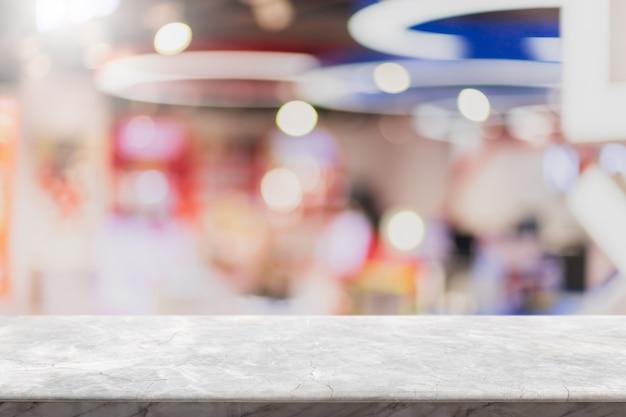 Dessus de table en pierre de marbre blanc vide et une fenêtre en verre floue, un café intérieur et une bannière de restaurant simulent un arrière-plan abstrait - peuvent être utilisés pour afficher ou monter vos produits.