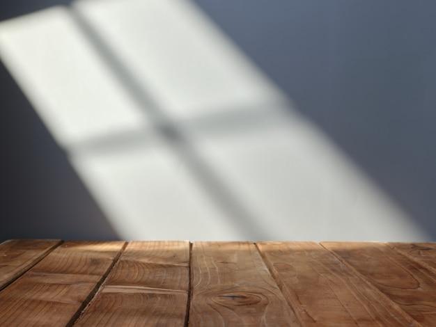 Dessus de table vide pour la présentation du produit avec mur en arrière-plan et lumière de la fenêtre