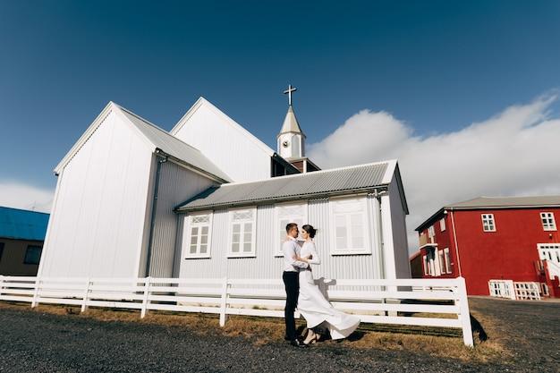 Destination islande mariage couple de mariage près d'une église noire en bois le marié embrasse la mariée blanche