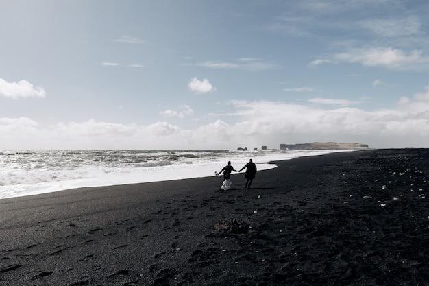 Destination mariage islande le couple de mariage longe la plage de sable noir de vik près du