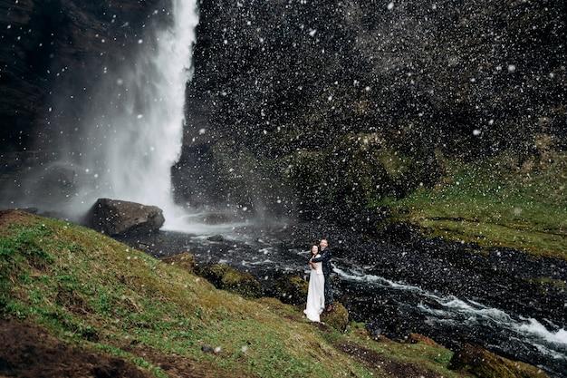 Destination mariage islande près de la cascade de kvernufoss couple de mariage se tient près de la cascade