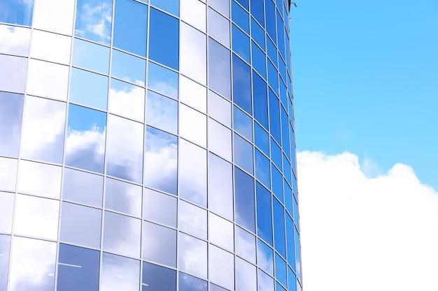Détail architectural de la façade avec de multiples reflets d'autres bâtiments et du soleil. extérieur du bâtiment moderne. abstrait de l'architecture
